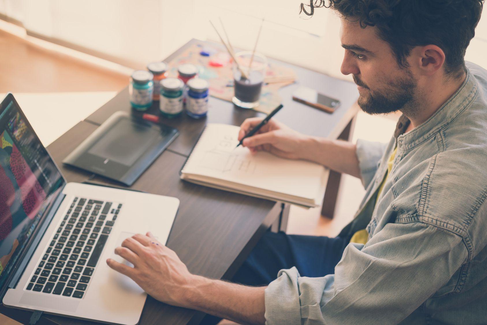 man making notes and using laptop