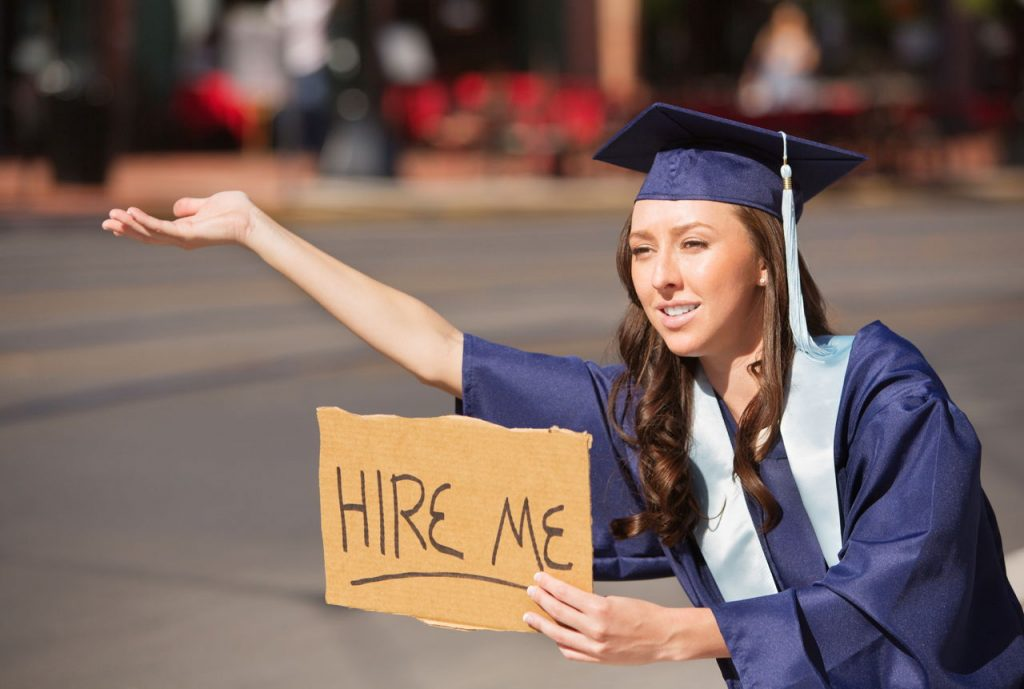 graduate with 'hire me' sign